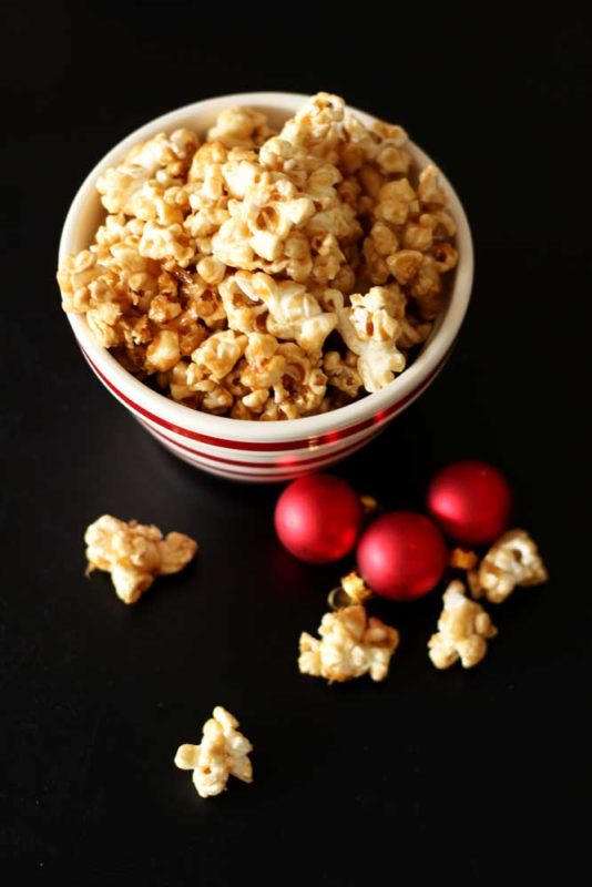 Bowl of Bourbon Caramel Popcorn sitting on a black table, popcorn pieces and red Christmas balls on table.