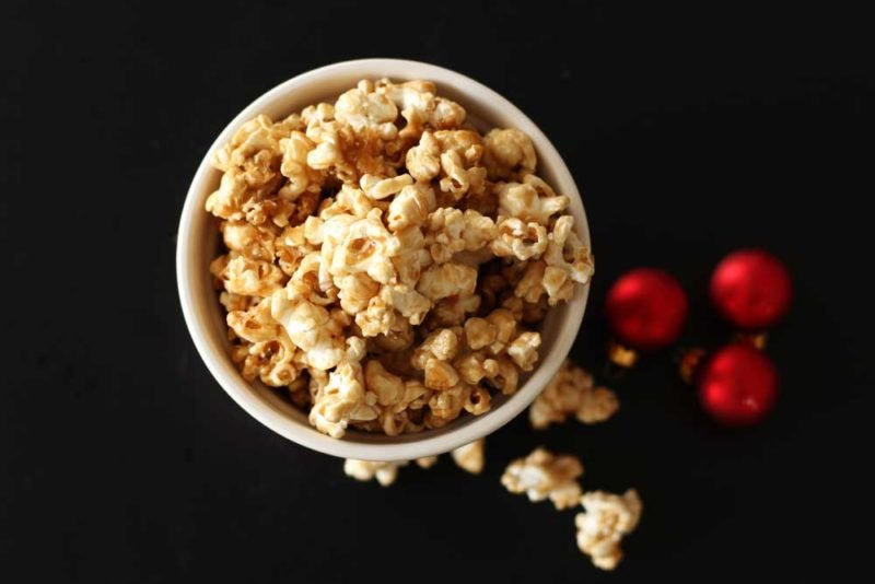 Bowl of Bourbon Caramel Popcorn sitting on a black table, red Christmas balls and pieces of popcorn on table.