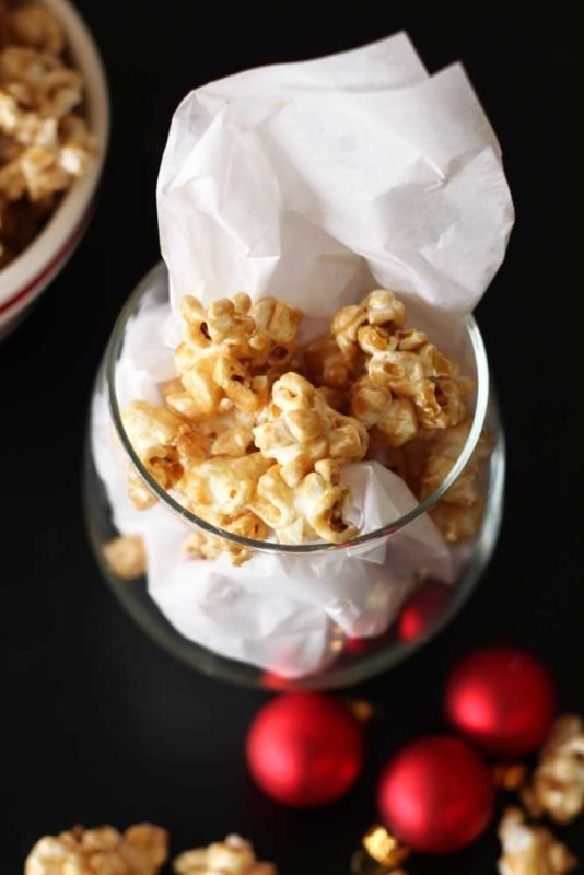 Short glass containing Bourbon Caramel Popcorn, red Christmas balls and bowl of popcorn on black table.