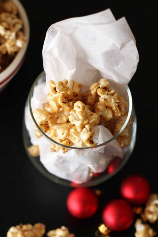 Short glass with white tissue paper containing Bourbon Caramel Popcorn, red Christmas balls and bowl of popcorn on black table.