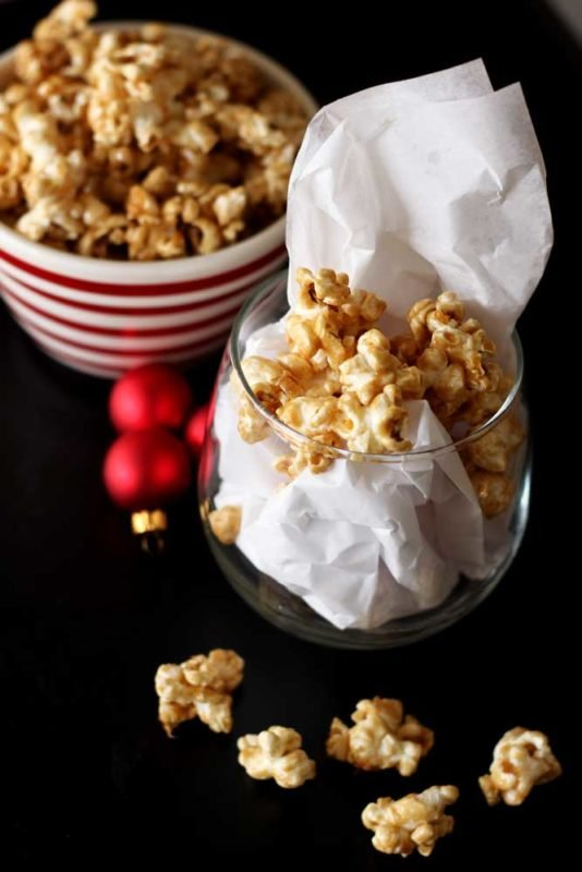 Short glass containing Bourbon Caramel Popcorn, red Christmas balls and bowl of popcorn on black table. White tissue paper in glass.