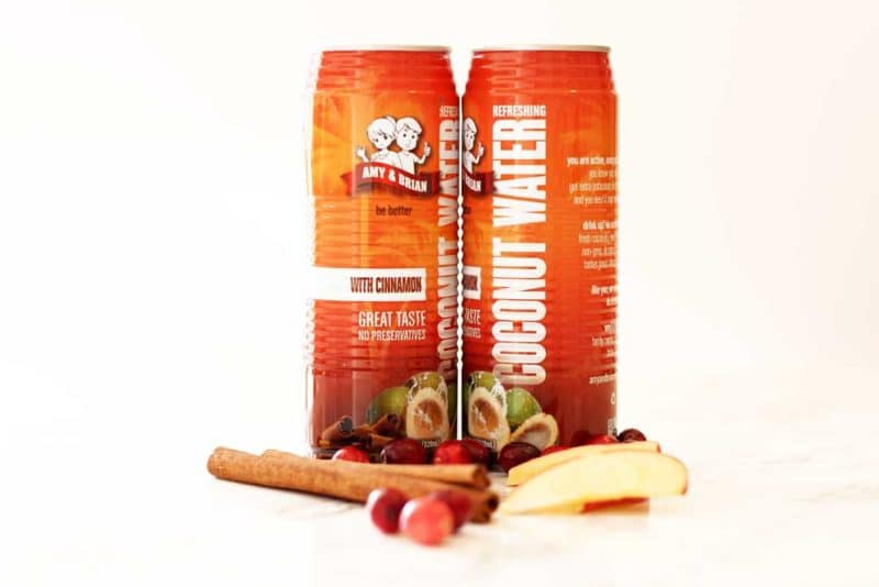 2 Cans of Amy & Brian's Coconut Water with Cinnamon, apple slices, cranberries and cinnamon sticks on table.