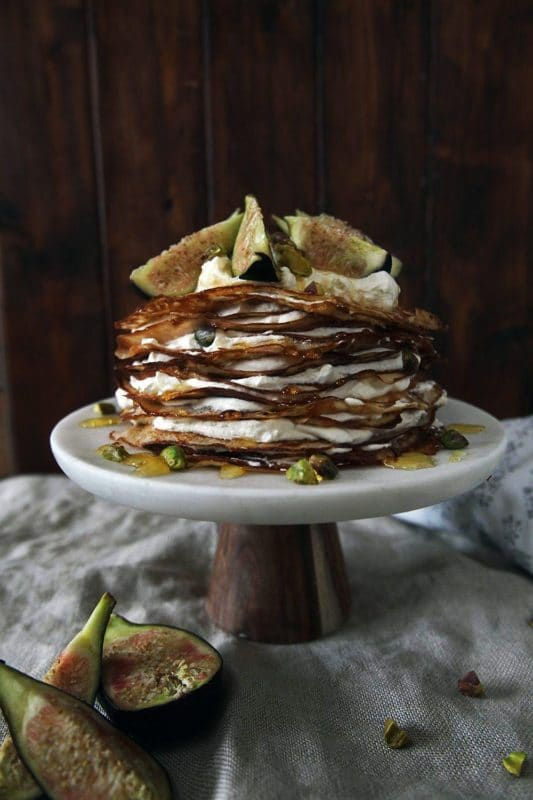 White marble cake dish containing a Gluten Free Fig & Mascarpone Crepe Cake, figs on side.