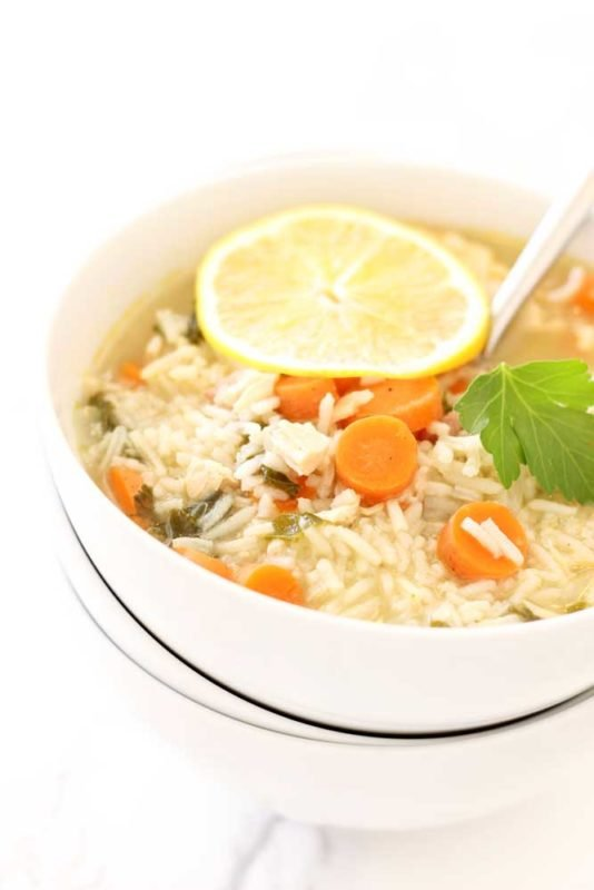 Three white bowls stacked and filled with Leftover Turkey and Rice soup, topped with rice, carrots and a lemon slice.
