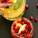 Short glass of Cinnamon Apple White Sangria topped with cranberries, pitcher on black ta