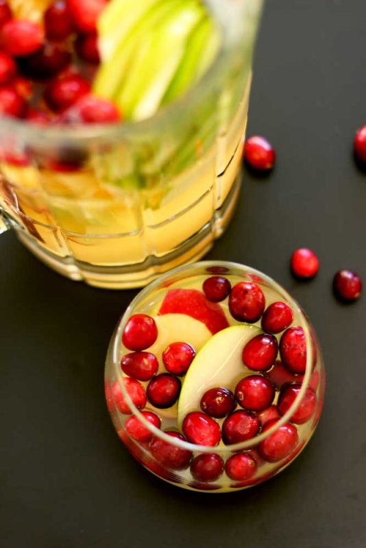 Short glass of Cinnamon Apple White Sangria topped with cranberries, pitcher on black table.