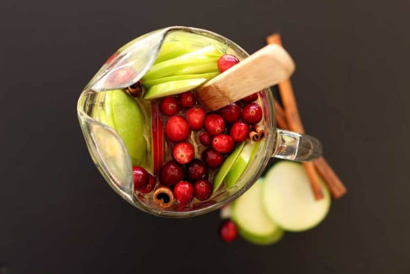 Pitcher of Cinnamon Apple White Sangria sitting on a black table, topped with cranberries, apple slices and cinnamon sticks.