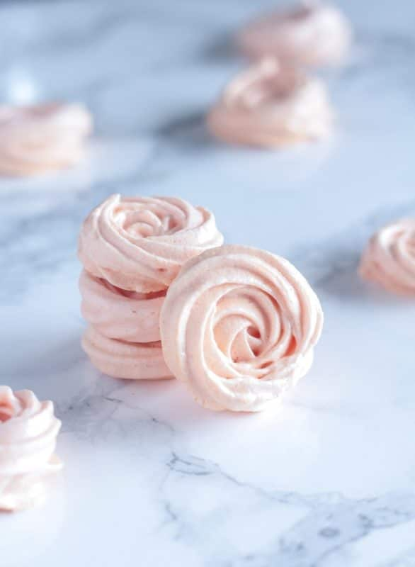 3 Gluten Free Rose Meringues sitting on a white marble table.