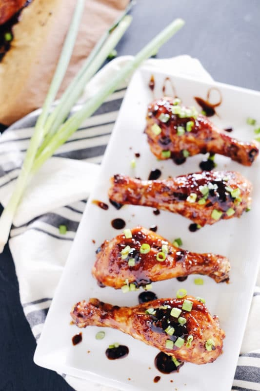 A white dish containing 4 Balsamic Glazed Chicken Drumsticks sitting on a gray and white napkin on a gray table.