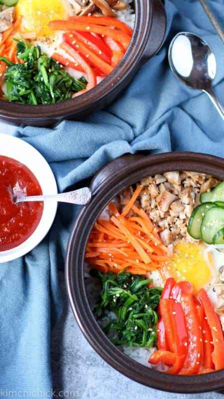 Black dish containing Bibimbap served with white rice topped with sautéed and seasoned vegetables sitting on a blue table, sweet and sour sauce on side with silver spoon for serving.