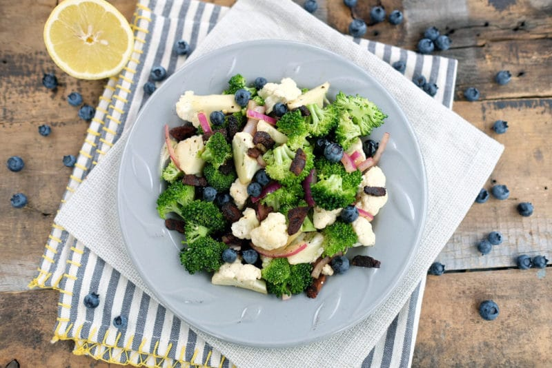 White bowl containing Broccoli Cauliflower Salad topped with blueberries sitting on a blue and white striped napkin, lemon wedge on side.
