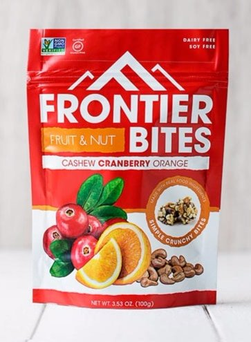 A red and white package of Frontier Bites Cashew, Cranberry and Orange Granola Clusters.