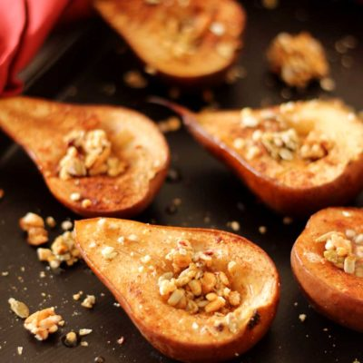 Brown flexipan containing 6 baked pears topped with granola, red napkin around pan.