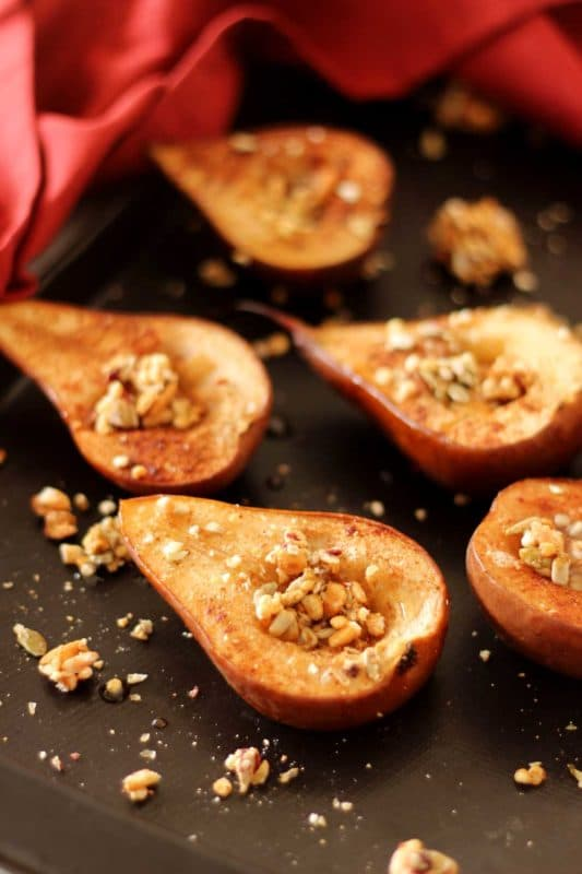 Brown pan containing 5 baked pear halves topped with granola, red napkin in background.
