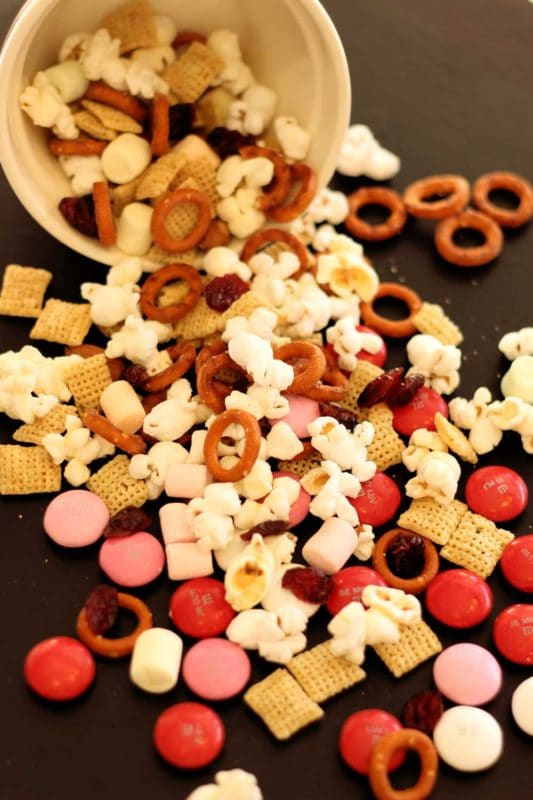 Black table with a spilled bowl of popcorn snack mix containing popcorn, chex cereal, pretzels, dried cranberries and M&M.s