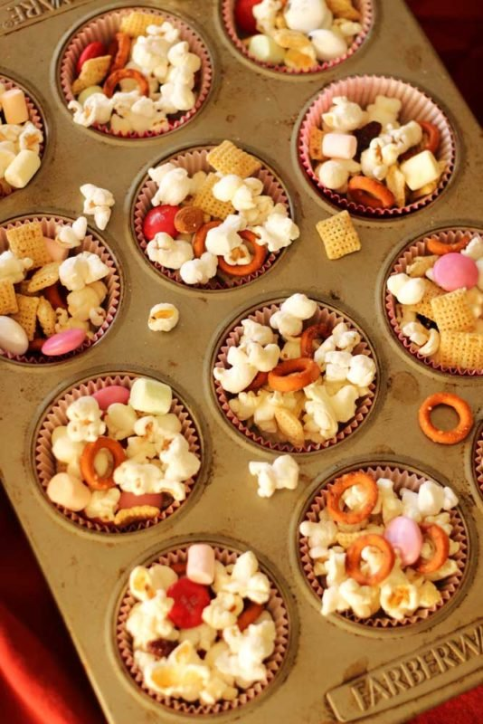 Muffin tin filled with 12 muffin cups of popcorn, chex, pretzels, marshmallows and M&Ms!