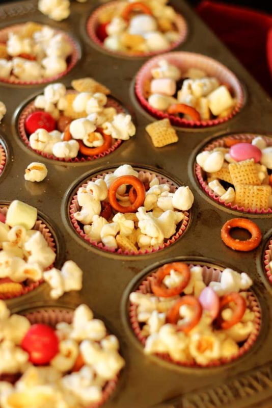 Cupcake tin filled with a popcorn snack containing popcorn, pretzels and M&Ms.