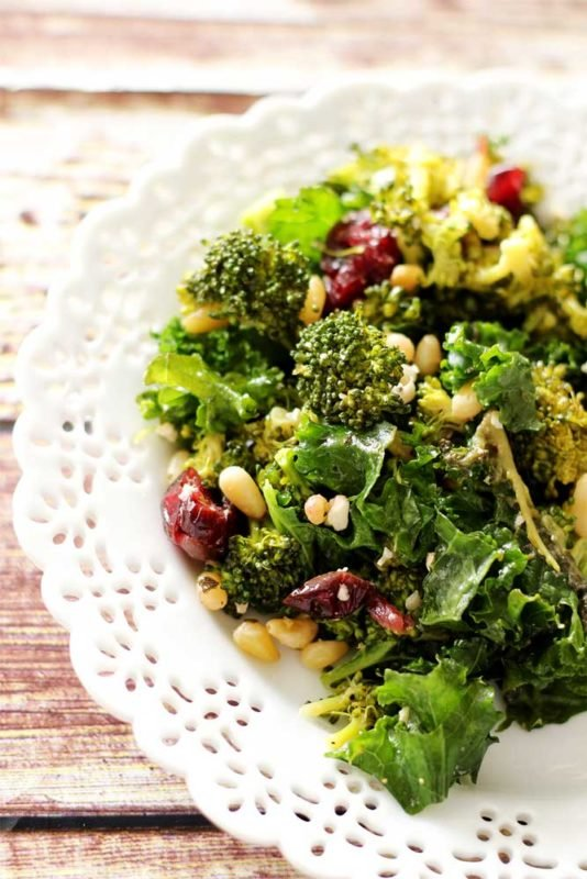 White plate sitting on a wooden table containing a kale and broccoli salad with pine nuts and dried cranberries.