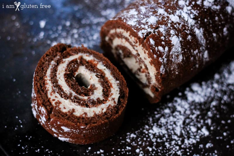 Sliced Chocolate Roulade sitting on a black table with sprinkled powdered sugar.