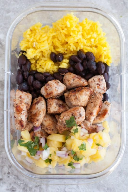 A clear tupperware bowl containing jerk chicken, black beans, rice and mango salsa.