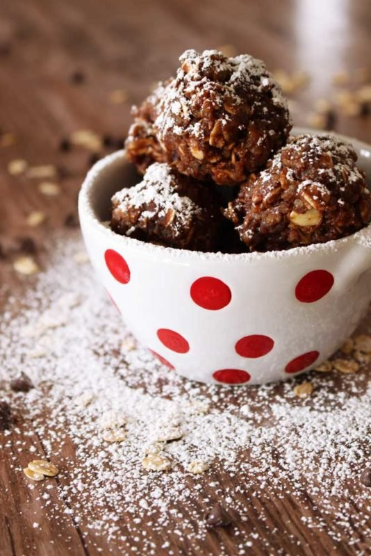 White bowl with red polka dots containing 3 Quinoa Protein Bites sitting on a brown table, sprinkled powdered sugar.