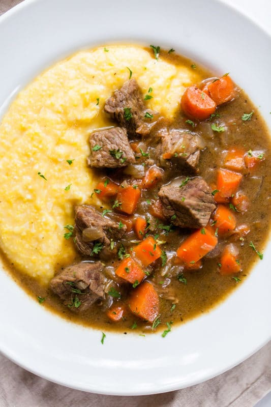 White bowl containing Beef Stew with Cheesy Polenta topped with carrots and parsley.