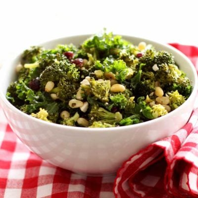 White bowl containing broccoli and kale salad with pine nuts and feta cheese on top, sitting on a red and white gingham napkin.