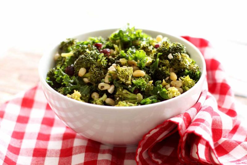 White bowl containing broccoli and kale salad with pine nuts and feta cheese on tip, sitting on a red and white gingham napkin.