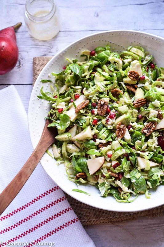 White bowl containing Brussel Sprout Salad with Pear and Pomegranate sitting on a brown table, wooden spoon in bowl and red striped napkin on side.