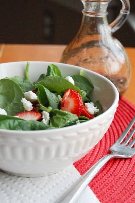 A white bowl containing spinach leaves, feta cheese and strawberries sitting on red place mat, silver fork and balsamic dressing in background.