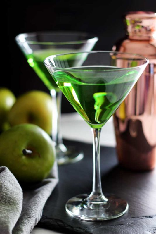 Two martini glasses filled with a Green Apple Martini Cocktail sitting on a black table, cocktail mixer and three green apples in the background.