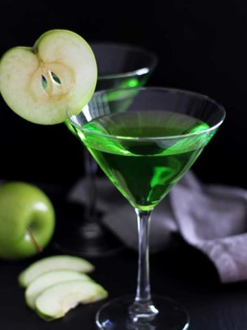 Two Martini glasses filled with a Green Apple Martini drink sitting on a black table, gray napkin and green apple slices in the background.