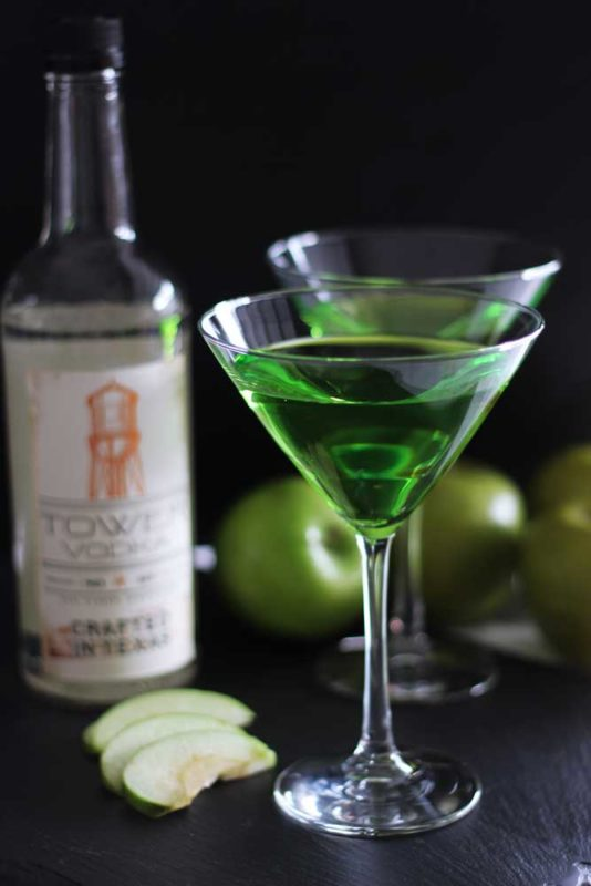 Two martini glasses filled with a Green Apple Martini cocktail sitting on a black table, Tower Vodka Bottle and green apples on the table.