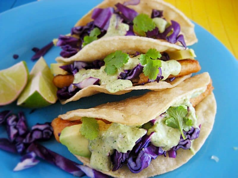 Three fish tacos sitting on a blue plate on a yellow table, topped with purple cabbage, cilantro and two lime wedges.