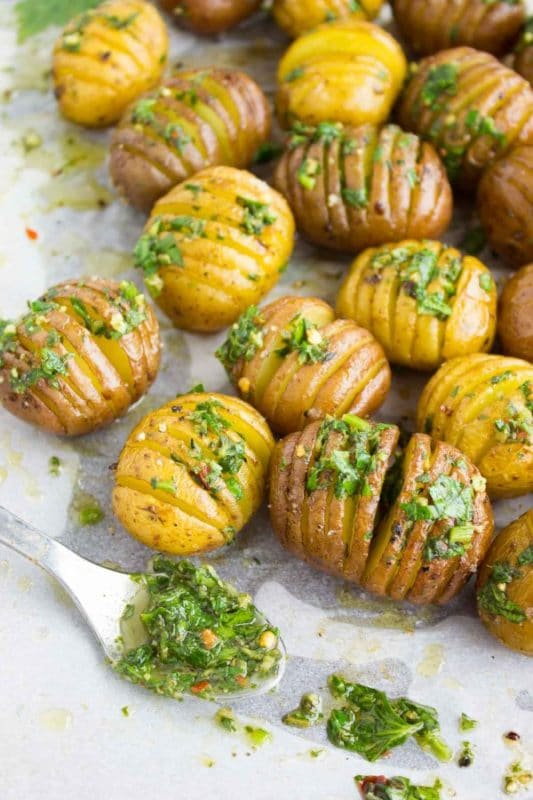 Eighteen sliced russet potatoes filled with an herb sauce, sitting on a white table with a spoonful of herbs.