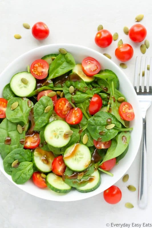 White bowl containing raw spinach, cucumbers, tomatoes and pumpkin seeds sitting on a white table with a fork, scattered tomatoes and pumpkin seeds on table.