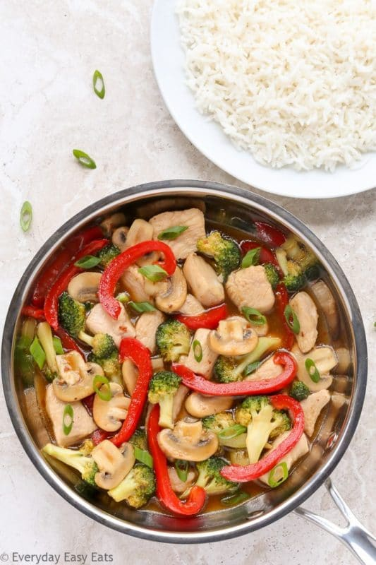 Pan containing chicken stir fry with broccoli and red peppers, sitting on a white table with a bowl of white rice in the background.