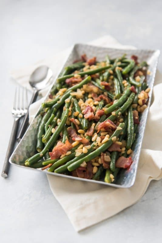 White dish containing green beans topped with bacon and pine nuts, sitting on a white napkin with a fork and spoon.