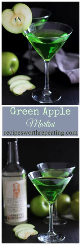 Two martini glasses filled with a Green Apple Martini Cocktail topped with sliced green apples, Tower Vodka Bottle sitting on black table with gray napkin.
