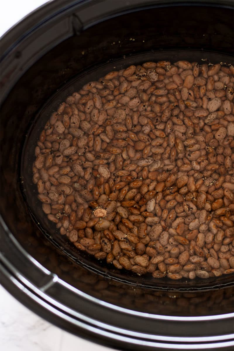 Pinto Beans in a slow cooker covered with water, salt and pepper in water.