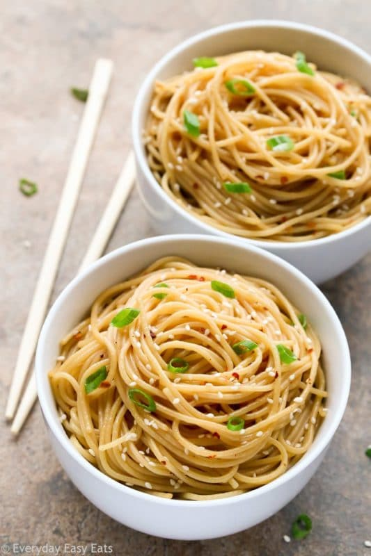 Two white bowls containing sesame noodles topped with sesame seeds and scallions sitting on a brown table, chopsticks and scallions scattered on the table.