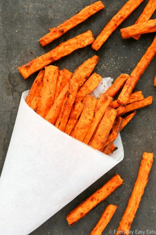 A white cone containing baked sweet potato fries, sitting on a gray marble table sprinkled with sea salt.