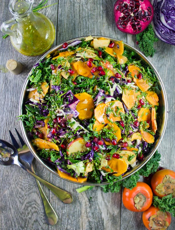 A blow bowl of kale, apple and persimmons sitting on a wooden table, crossed forks and vinaigrette dressing.