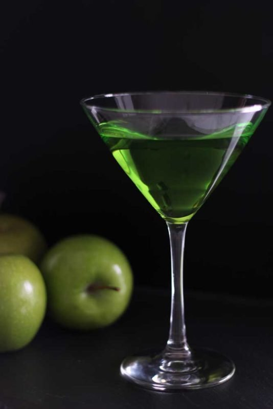Martini glass filled with a Green Apple Martini Cocktail sitting on a black table, three green apples sitting on black table.