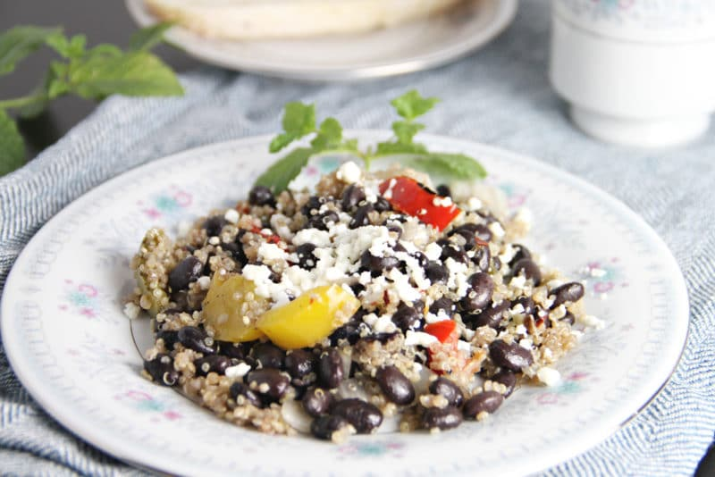 Quinoa and black beans topped with yellow and red peppers and feta cheese on a white plate.