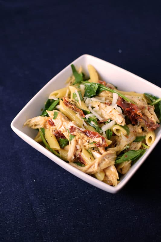 White bowl containing penne pasta with spinach and sun dried tomatoes, sitting on a navy blue table.