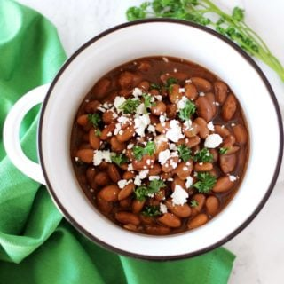 Pinto Beans in a white bowl sitting on a white table with a green napkin topped with feta cheese and fresh parsley.