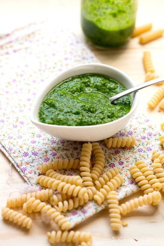 A white bowl of pesto with a serving spoon sitting on a table with scattered rotini pasta.