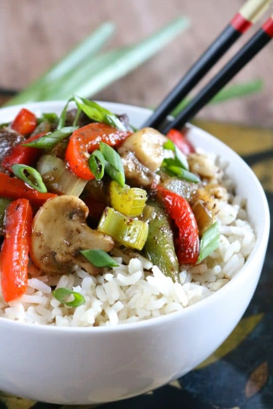 White bowl containing white rice with sauteed vegetables, black chopsticks in the bowl. Instant Pot Recipe.