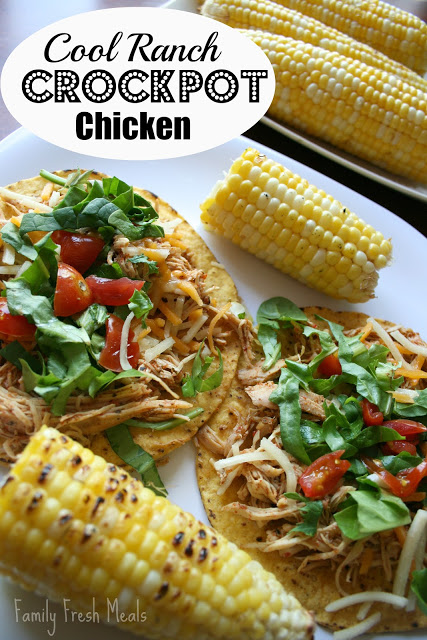 A white plate featuring cool ranch chicken on tostadas, topped with tomatoes and lettuce, served with corn on the cob.
